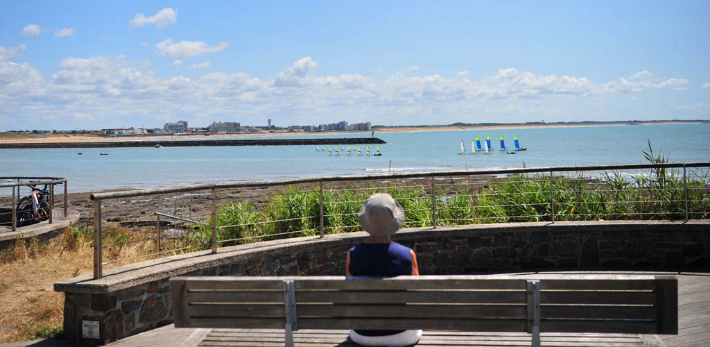 Woman sitting on a bench in front of the sea on the cornice of Saint-Hilaire-de-Riez